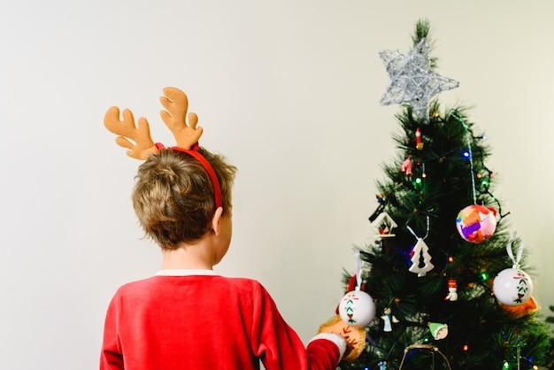 Criança em traje de papai noel, preparando a árvore de natal, de costas e branco com copyspace.