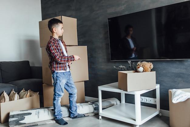 Criança em um apartamento novo, esperando assistir filmes com caixas de desempacotamento
