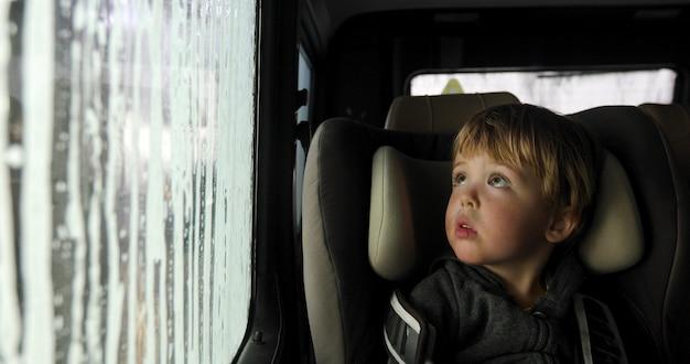 Criança em um assento de carro na lavagem de carros
