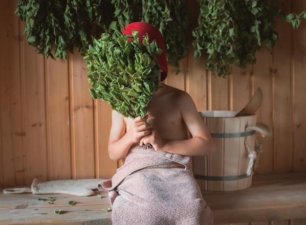 Criança em um banho russo com uma vassoura de bétula