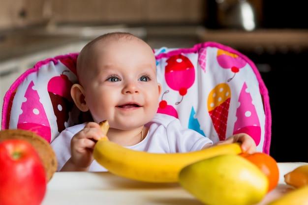 Criança, em, um, cadeira alta, comer, fruta, e, sorrindo