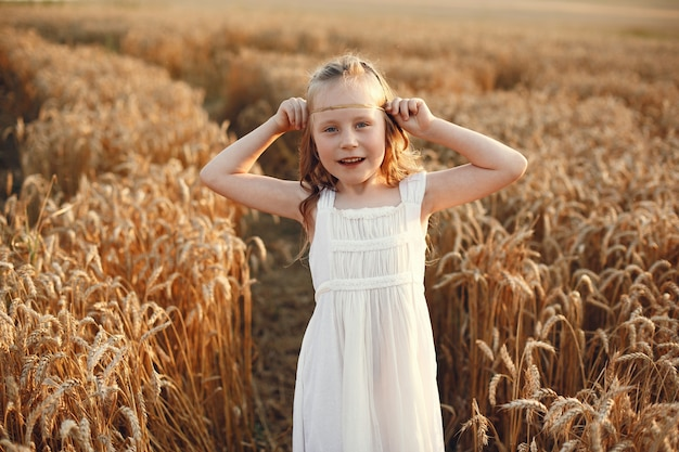 Criança em um campo de trigo de verão. menina em um lindo vestido branco.
