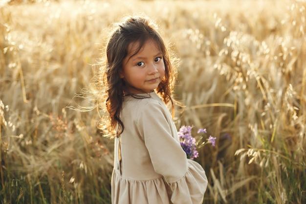 Criança em um campo de verão. menina com um lindo vestido marrom.
