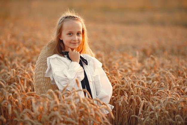 Criança em um campo de verão. menina em um lindo vestido branco.