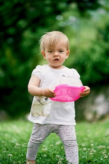 Criança em um gramado verde com um recipiente de plástico para comida nas mãos