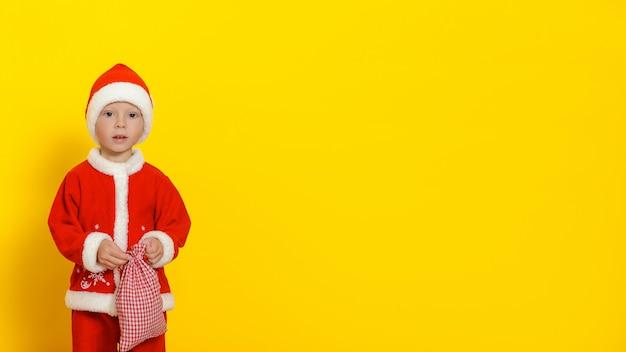 Criança em um terno vermelho de ano novo com uma sacola de presentes nas mãos olhando misteriosamente para a câmera