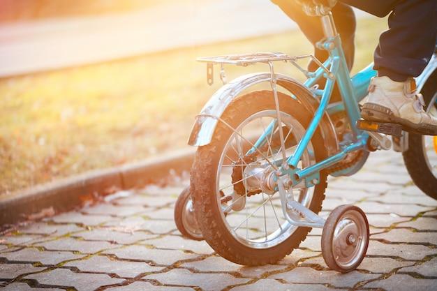 Criança em uma bicicleta em dia de sol. vista traseira.
