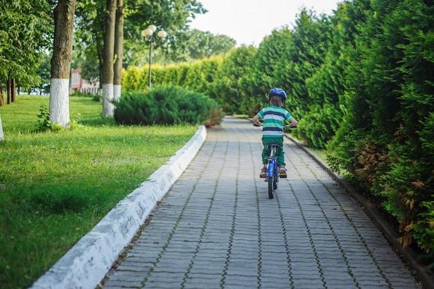 Criança em uma bicicleta na estrada asfaltada no dia de verão no parque. vista traseira
