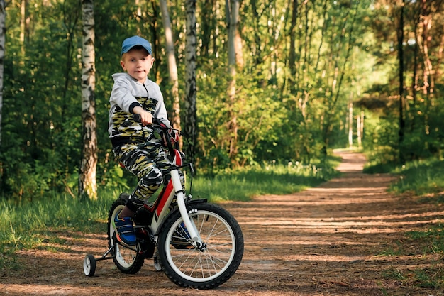 Criança em uma bicicleta na floresta no início da manhã. rapaz, andar de bicicleta ao ar livre no capacete