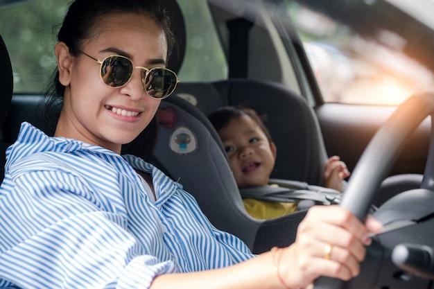 Criança em uma cadeira de segurança perto de mãe que se senta na frente sentado do carro