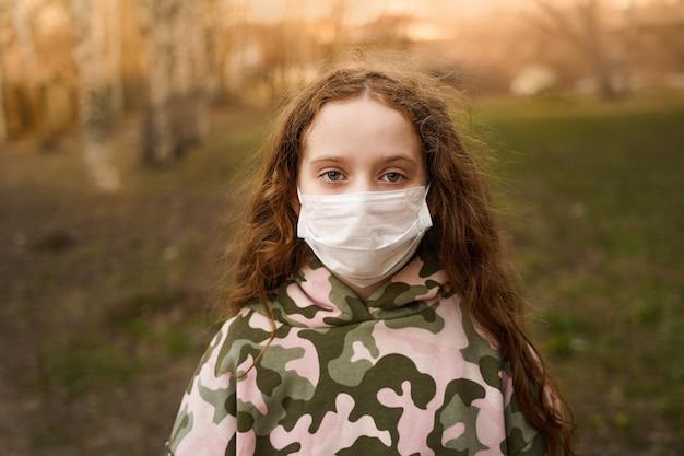 Criança em uma máscara médica ao ar livre.
