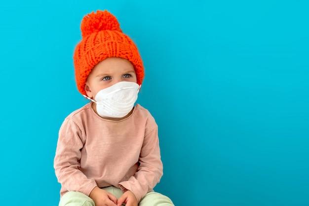 Criança em uma máscara médica sobre um fundo azul