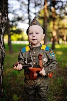 Criança em uniforme militar contra o fundo da natureza