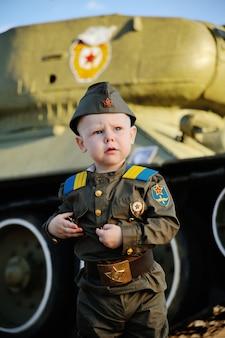 Criança em uniforme militar no fundo do tanque
