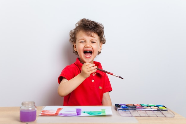 Criança emocional e alegre, um menino, senta-se à mesa com tintas e pincel e desenha em uma folha de papel.