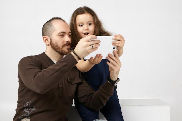 Criança emocionalmente feminina abrindo amplamente a boca, maravilhada com o novo tablet digital, usando-o com seu pai jovem e moderno com barba por fazer