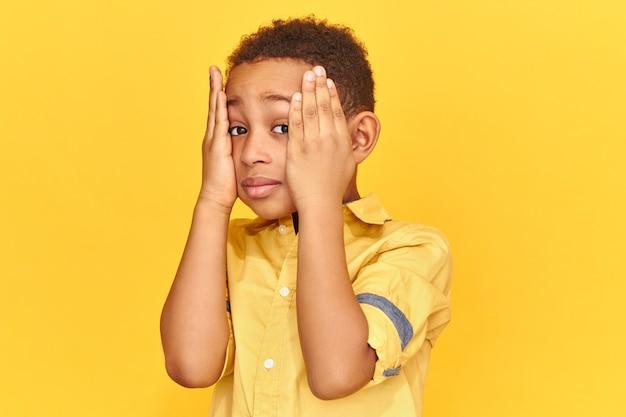 Criança emocionalmente morena mantendo as mãos no rosto tendo olhar chateado e esquecido, estando estressada por causa de notas ruins na escola.