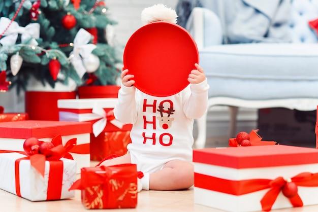 Criança encantadora, sentada entre presentes de feriado em um quarto aconchegante e cobriu o rosto com uma capa de papel circular vermelha da caixa.