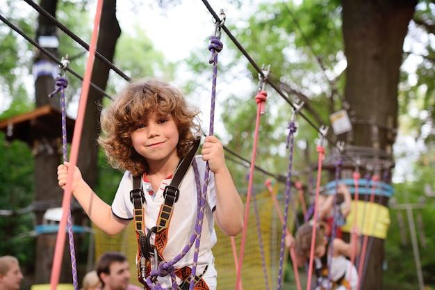 Criança encaracolada bonito em um parque de corda