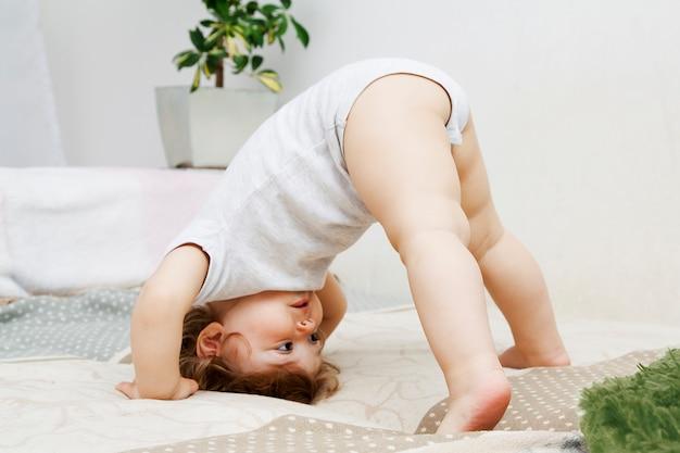 Criança encaracolada engraçada se diverte jogando em casa de pé na cabeça
