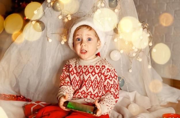 Criança engraçada assistindo a um vídeo chat com o papai noel em uma sala decorada