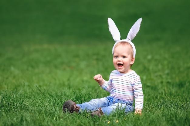 Criança engraçada com orelhas de coelho procurando ovos na grama caça aos ovos de páscoa ostern
