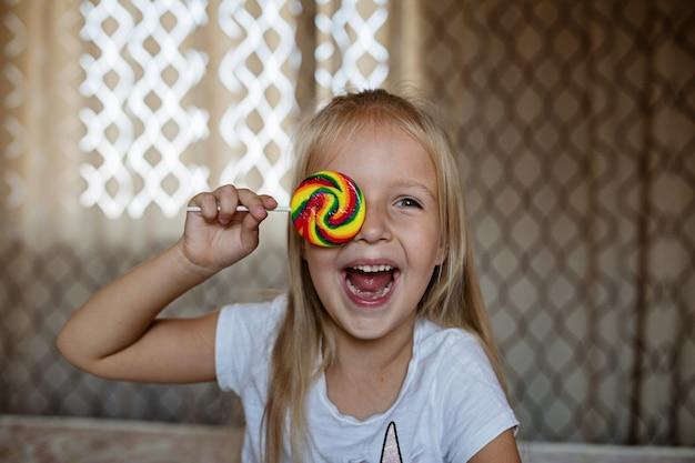 Criança engraçada com pirulito de doces