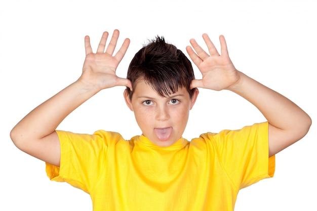 Criança engraçada com t-shirt amarela zombando isolado no fundo branco