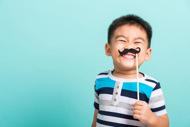 Criança engraçada e feliz segurando um bigode preto
