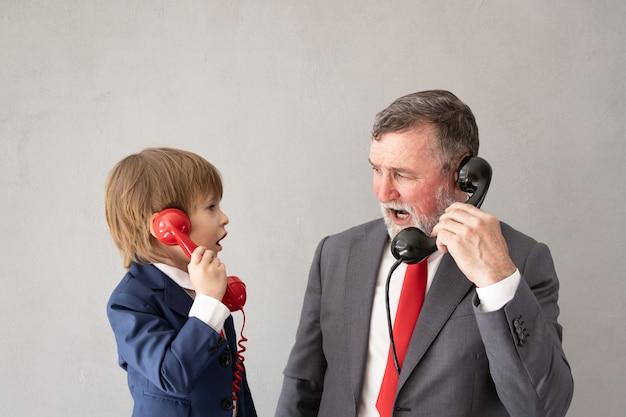 Criança engraçada e homem sênior fingem ser empresários. avô e criança brincando em casa. educação, start up e conceito de ideia de negócio