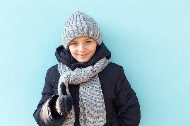Criança engraçada e sorridente mostrando os polegares, pronta para as férias de inverno. rapaz elegante no boné cinza de inverno e lenço em pé contra a parede azul.