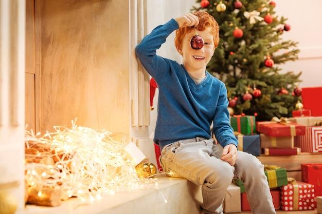 Criança engraçada escondendo o olho direito atrás de uma bola vermelha brilhante e fazendo careta enquanto está sentado ao lado de uma lareira decorativa e fica animado com o natal.
