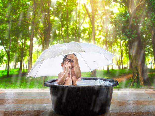Criança engraçada feliz com guarda-chuva sob a chuva.