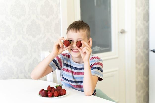Criança engraçada ri e coloca morangos em vez de olhos