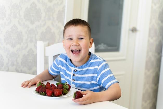 Criança engraçada ri e come morangos. primavera. abril maio.