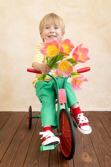 Criança engraçada segurando um buquê de flores.