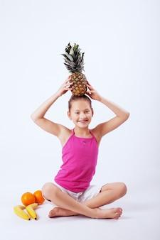 Criança engraçada tem laranjas, abacaxi e banana.