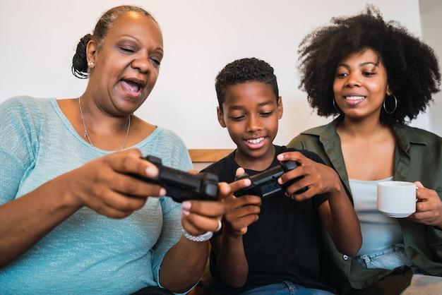 Criança ensinando avó e mãe para jogar videogame.