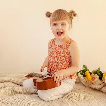 Criança entusiasmada que guarda a guitarra