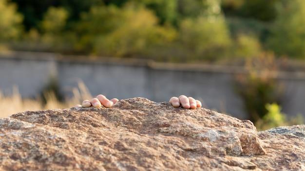 Criança escalando rochas com apenas as pontas dos dedos aparecendo sobre a borda com água visível abaixo