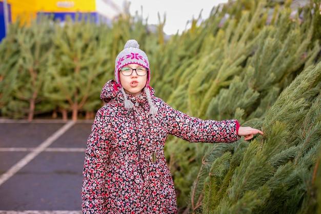 Criança, escolhendo e decorando uma árvore de natal