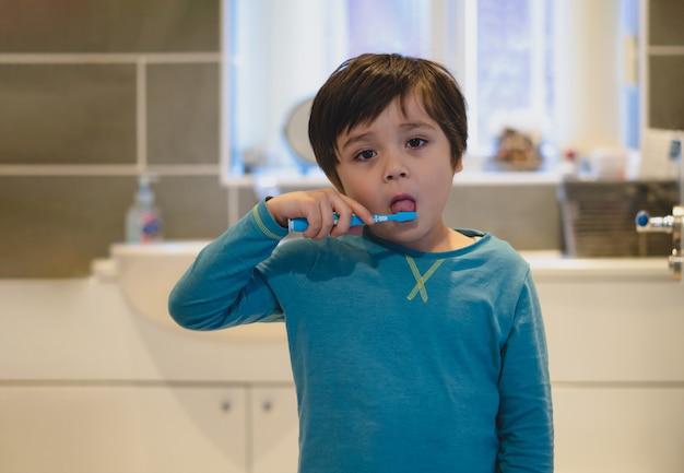 Criança escovando dentes e língua no banheiro