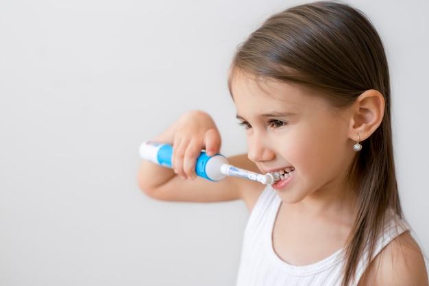 Criança escovando os dentes com escova de dentes elétrica.