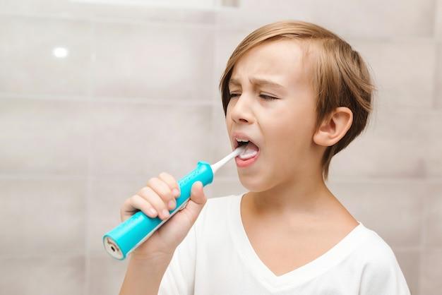 Criança escovando os dentes com escova elétrica no banheiro. higiene dental todos os dias. cuidados de saúde, infância e higiene dentária.