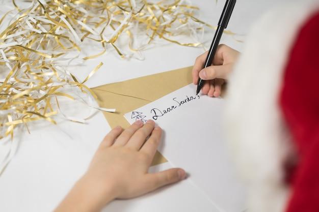 Criança escreve carta para o papai noel no chapéu de papai noel, conceito de natal