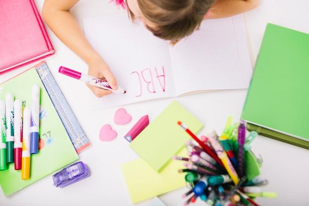 Criança escrevendo letras no bloco de notas
