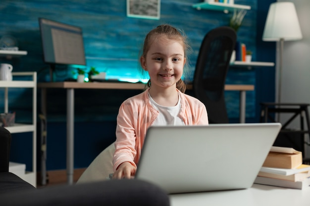 Criança esperta digitando em um laptop moderno na mesa de casa