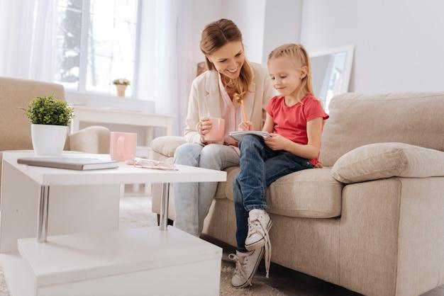 Criança esperta. mãe alegre e simpática, segurando uma xícara de chá e olhando para a filha, enquanto a ajuda nos estudos