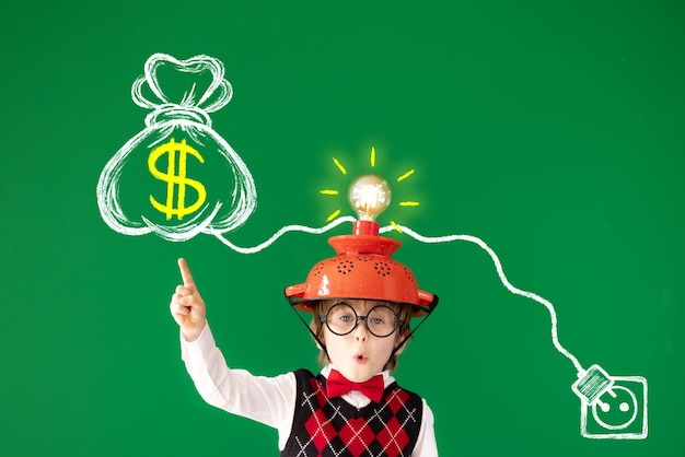 Criança esperta tem uma ideia retrato de criança contra o quadro verde
