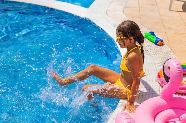 Criança espirra água na piscina. foco seletivo. miúdo.